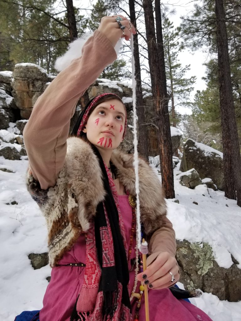 A person in Old Norse garb spinning yarn in nature